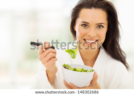 beautiful young woman in bathrobe eating healthy food