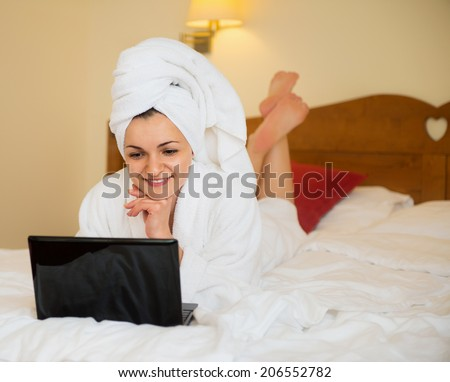 Beautiful young woman in bathrobe working with laptop in bed  - stock photo