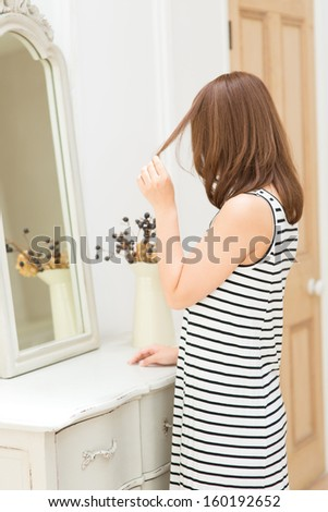 Beautiful young woman in bathroom looking at herself in mirror