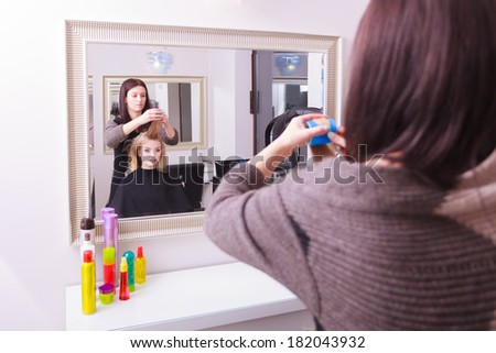 Beautiful young woman in beauty salon. Blond girl with hair curlers rollers by hairdresser. Hairstyle. Reflection in mirror.