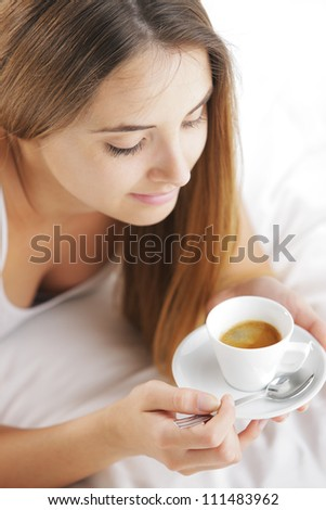 Beautiful young woman in bed drinking cofee in the morning. - stock photo