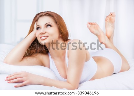 Beautiful young woman in bed in the early morning - stock photo