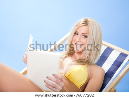 Beautiful young woman in bikini lying on a deckchair and reading a book at the beach - stock photo