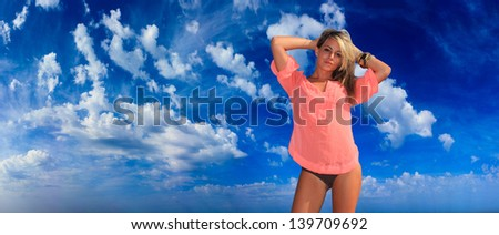 Beautiful young woman in bikini on bright blue shky background