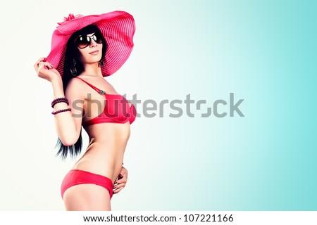Beautiful young woman in bikini over blue sky. - stock photo
