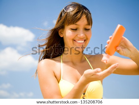 beautiful young woman in bikini smear protective cream on the skin on the beach under the sun - stock photo
