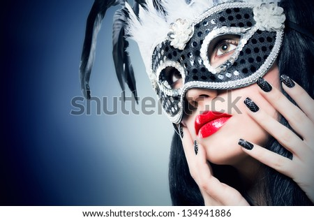 Beautiful young woman in black carnival mask with manicure - stock photo