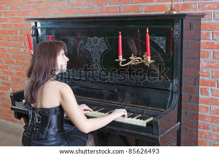 beautiful young woman in black dress playing the piano - stock photo