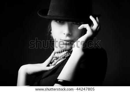 Beautiful young woman in black hat.Retro portrait - stock photo