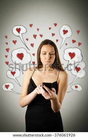 Beautiful young woman in black is using a mobile phone. Valentine day concept. - stock photo