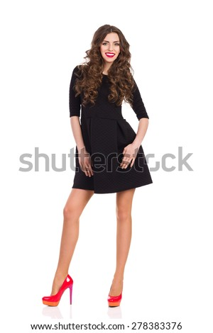 Beautiful young woman in black mini dress and red high heels posing. Full length studio shot isolated on white.