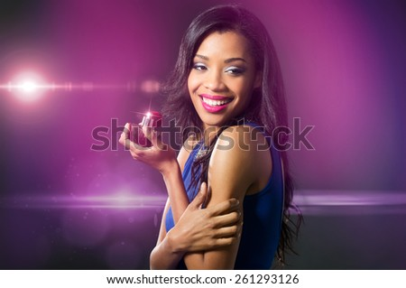 Beautiful young woman in blue dress holding perfume bottle  - stock photo