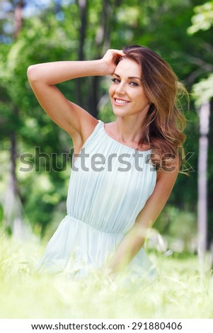 beautiful young woman in blue dress sitting on grass - stock photo