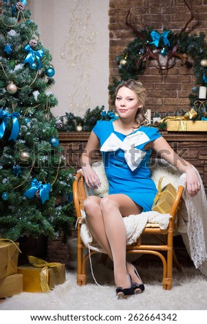 Beautiful young woman in blue dress sitting on the chair near a fir-tree - stock photo