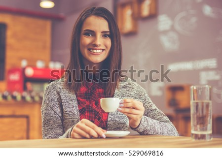 Beautiful young woman in casual clothes drinking coffee and smiling while sitting in a cafe