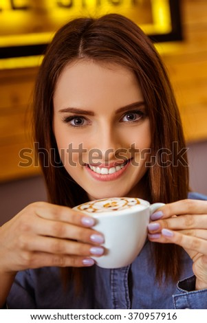 Beautiful young woman in casual clothes drinking coffee and smiling while sitting in a cafe, close-up