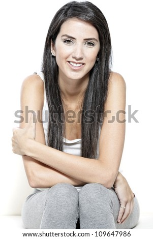 Beautiful young woman in casual clothes resting on white sofa at home - stock photo