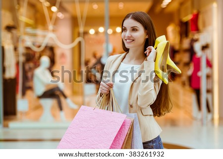 Beautiful young woman in casual clothes smiling, holding shopping bags and pair of stylish shoes while standing in mall - stock photo