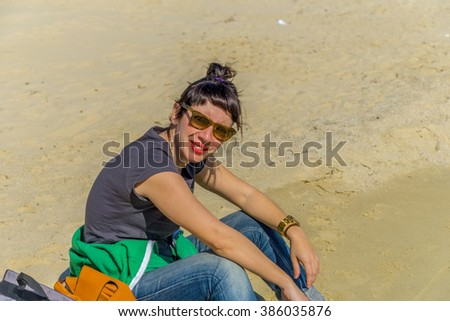 Beautiful young woman in casual outfit enjoying the sun in a beautiful beach in Mykonos, Greece. - stock photo
