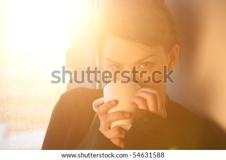 Beautiful young woman in casual wear dreaming with cup of hot coffee over window. Sun beam. - stock photo