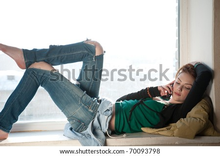 Beautiful young woman in casual wear with cell phone laying on window. Over city. - stock photo