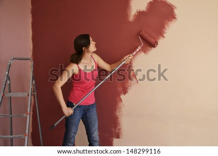 Beautiful young woman in causal clothes painting a wall with red paint and a roller - stock photo