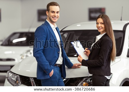 Beautiful young woman in classic suit and handsome young man are smiling and looking at camera while examining a car in a motor show