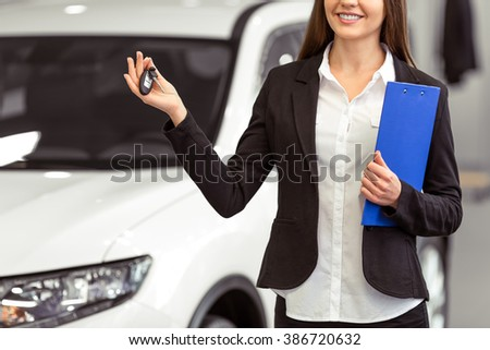 Beautiful young woman in classic suit is smiling, looking at camera and offering car keys while presenting car in a motor show, cropped