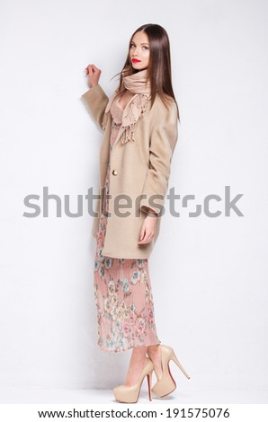 Beautiful young woman in coat posing in studio - stock photo