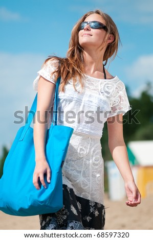 Beautiful young woman in dress and sunglasses walking on sand beach with bag on sunny summer day