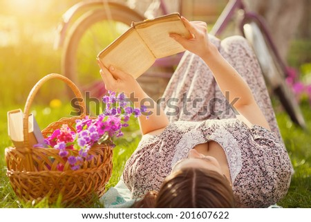 Beautiful young woman in dress laying on grass with basket of flowers and reading book near old vintage bicycle - stock photo