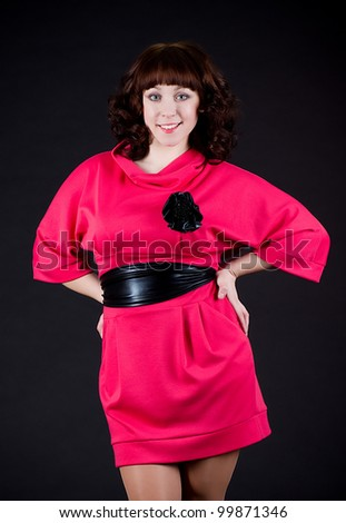 Beautiful young woman in dress on dark background. - stock photo