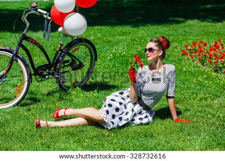 Beautiful young woman in dress retro pin-up style having rest on the grass in summer park near her stylish lady city bicycle decorated with red and white balloons. - stock photo