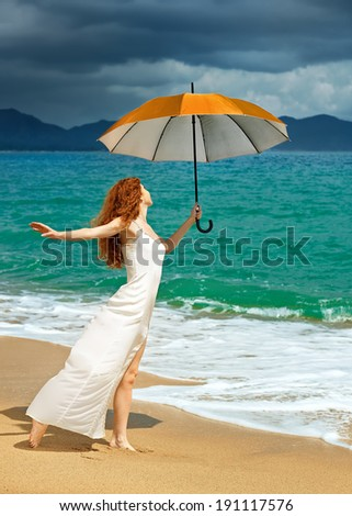 Beautiful young woman in dress standing on the beach with an umbrella before the rain against a background of dramatic clouds - stock photo
