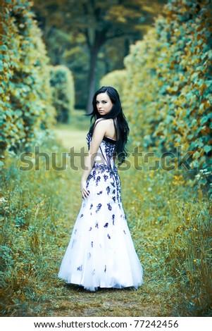 Beautiful young woman in elegant dress in dramatic magic park - stock photo