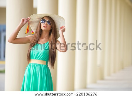 Beautiful young woman in elegant hat and sunglasses posing - stock photo