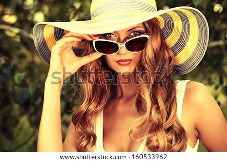 Beautiful young woman in elegant hat and sunglasses posing outdoor. - stock photo