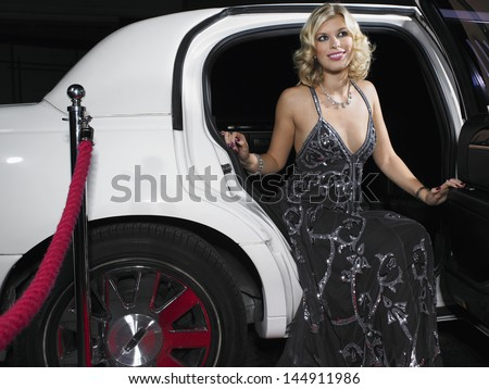 Beautiful young woman in evening wear getting out of limousine - stock photo