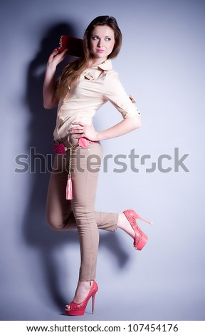 Beautiful young woman in fashion clothes on background - stock photo