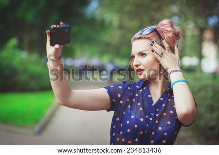 Beautiful young woman in fifties style taking picture of herself - stock photo
