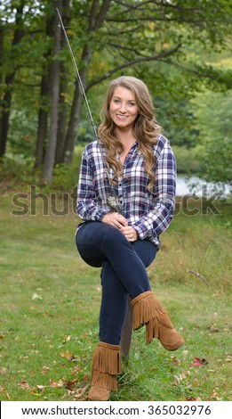 Beautiful young woman in flannel shirt with fishing pole - country girl gone fishing'