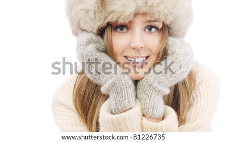 Beautiful young woman in fur cap and sweater, isolated on white background.