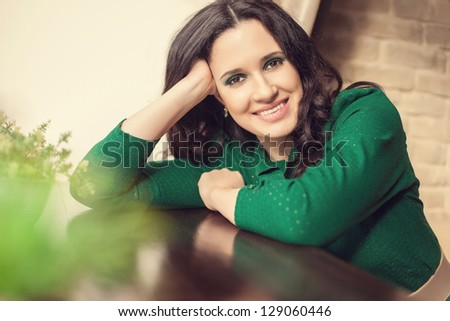Beautiful young woman in green shirt sitting at dining table at home