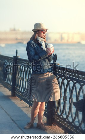 Beautiful young woman in hat and scarf enjoy sunlight outdoor in the city - stock photo