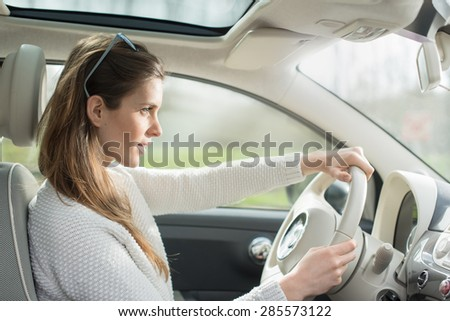 beautiful young woman in her car driving on a country road