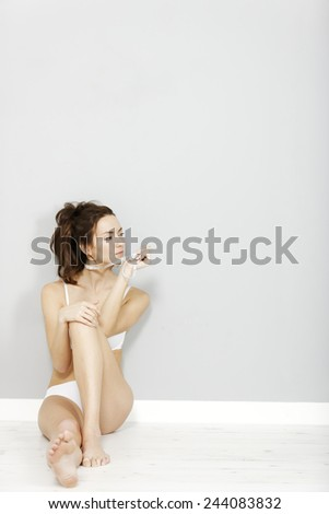 Beautiful young woman in her underwear holding a white tape measure - stock photo