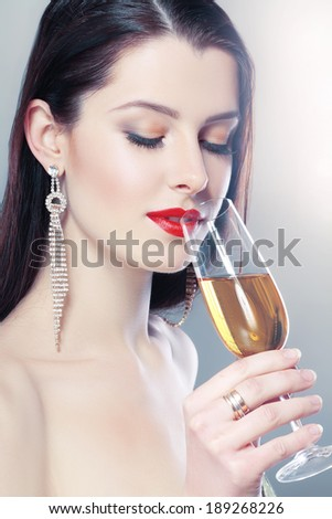 Beautiful young woman in hold a glass of champagne soft colors - stock photo