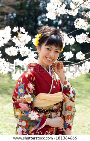 Beautiful young woman in Japanese Kimono viewing cherry blossoms in the garden. Spring in Japan.