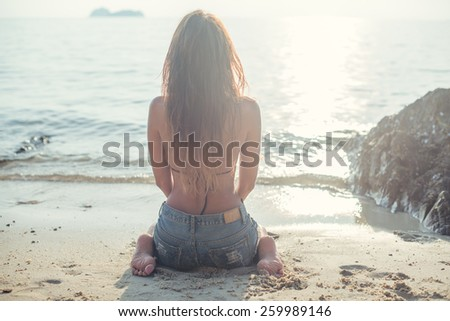 beautiful young woman in jeans shorts with resting at beach front of the sea in summer sitting on sand warm colors filter instagram - stock photo
