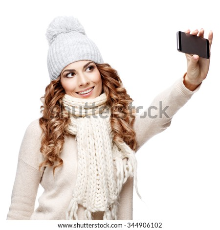 Beautiful young woman in knitted wool sweater smiling isolated on white